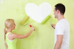 Paar bij hart het schilderen op muur Stock Foto's