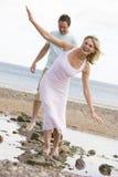 Paar bij het strand dat bij stenen en het glimlachen loopt Royalty-vrije Stock Foto's