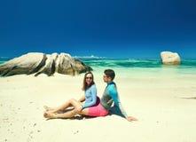 Paar bij tropisch strand die onbesuisde wacht dragen Stock Foto