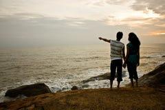 Paar bij zonsondergang op het strand Stock Afbeelding