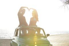 Paar bij zonsondergang op het strand met auto Royalty-vrije Stock Afbeeldingen