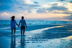 Paar bij zonsopgang op een strand stock foto's
