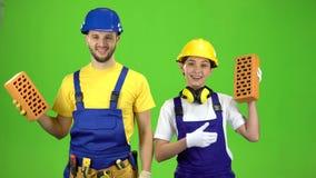 Paar bouwers die een baksteen in hun handen houden en hun vingers tonen Het groene scherm stock footage