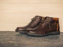 Paar bruine mensen` s klassieke schoenen op de donkere vloer houten muren Brutale mensen` s schoenen Royalty-vrije Stock Fotografie