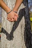 Paar in dag van de de handen de hete zomer van de liefdeholding buiten in de aard Jonge meisje en jongen met handen die samen bea royalty-vrije stock fotografie