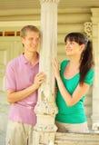 Paar dat aan kolom, glimlach op terras wordt geleund Royalty-vrije Stock Foto's