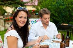 Paar dat BBQ in tuin in de zomer doet stock foto