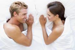 Paar dat in bed het glimlachen ligt royalty-vrije stock foto's