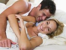 Paar dat in bed het lachen ligt Stock Foto's