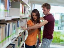 Paar dat in bibliotheek verdeelt Stock Afbeeldingen