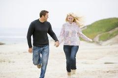 Paar dat bij de handen van de strandholding loopt Stock Foto's