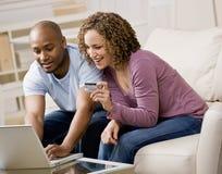 Paar dat creditcard gebruikt om online te winkelen stock foto's