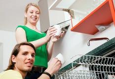 Paar dat de afwasmachine leegmaakt Stock Foto's