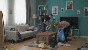 Paar dat de woonkamer na een partij schoonmaakt stock footage