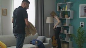 Paar dat de woonkamer na een partij schoonmaakt stock videobeelden