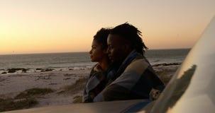 Paar dat in deken dichtbij pick-up bij strand tijdens zonsondergang 4k wordt verpakt stock videobeelden