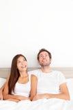 Paar dat denkend in bed kijkt Stock Afbeeldingen