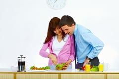 Paar dat een salade voor lunch voorbereidt stock foto