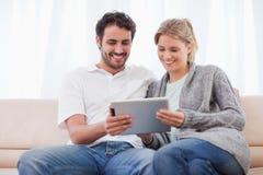 Paar dat een tabletcomputer met behulp van Stock Foto