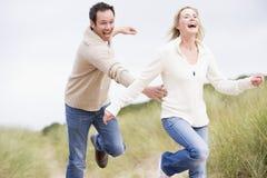 Paar dat elkaar door duinen achtervolgt Stock Fotografie