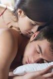 Paar dat en op het bed kust koestert Stock Fotografie