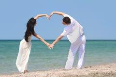 Paar dat hart maakt door wapens op strand Royalty-vrije Stock Afbeeldingen