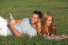 Paar dat in het park en het lezen ligt Stock Fotografie