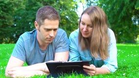 Paar dat in het park ligt en tablet-pc gebruikt stock video