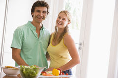 Paar dat in keuken voedsel het glimlachen voorbereidt Royalty-vrije Stock Afbeeldingen