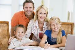 Paar dat kinderen met laptop helpt die thuiswerk doet stock afbeelding