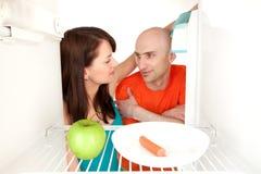 Paar dat in koelkast kijkt royalty-vrije stock foto's
