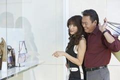 Paar dat koopwaar in winkelvenster bekijkt stock foto