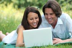 Paar dat laptop in park met behulp van Stock Foto