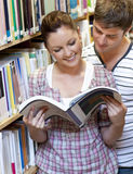 Paar dat lezend een boek in de bibliotheek geniet van Stock Afbeelding