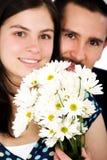 Paar dat met bloemen glimlacht Royalty-vrije Stock Afbeelding