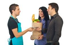 Paar dat met geld hun voedsel betaalt bij markt Royalty-vrije Stock Afbeeldingen