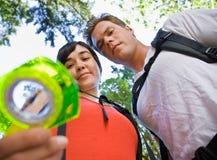 Paar dat met rugzakken kompas bekijkt Royalty-vrije Stock Foto