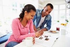 Paar dat Ontbijt heeft en Tijdschrift in Keuken leest Stock Fotografie