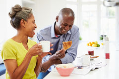 Paar dat Ontbijt heeft en Tijdschrift in Keuken leest Royalty-vrije Stock Foto's