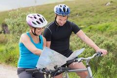 Paar dat op bergfietsen kaart leest stock afbeelding