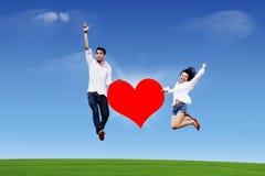 Paar dat op de hemel met hart springt Stock Foto's