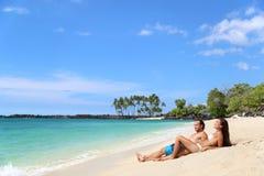 Paar dat op de ontspanning van de strandvakantie zonnebaadt royalty-vrije stock foto's