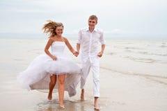Paar dat op een strand loopt stock foto's