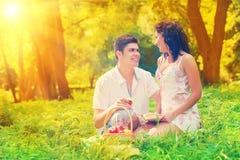 Paar dat op gras in park rust Stock Afbeeldingen