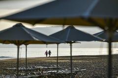 Paar dat op het strand bij zonsopgang loopt royalty-vrije stock afbeelding