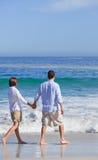 Paar dat op het strand onder de zon loopt Royalty-vrije Stock Foto