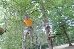 Paar dat op kabel in avonturenpark beklimt Stock Foto
