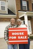 Paar dat op middelbare leeftijd a voor verkoopteken houdt. stock foto's