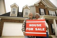 Paar dat op middelbare leeftijd a voor verkoopteken houdt. stock afbeeldingen