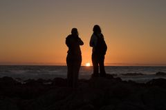Paar dat op oceaanzonsondergang let Stock Foto's